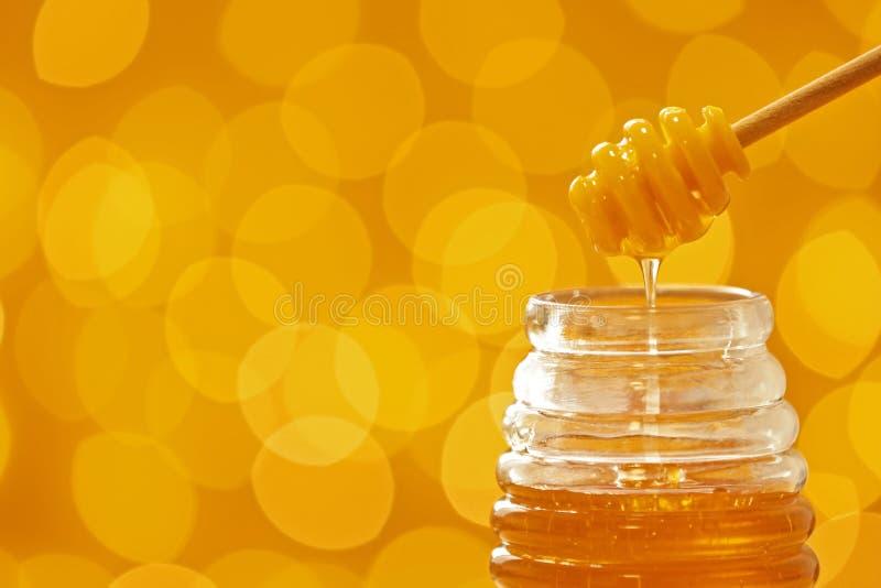 倾吐从浸染工的蜂蜜入在被弄脏的背景的瓶子 免版税库存照片
