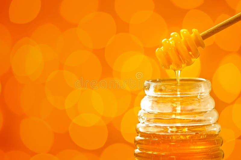 倾吐从浸染工的蜂蜜入在被弄脏的背景的瓶子 库存照片