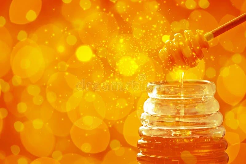 倾吐从浸染工的蜂蜜入在被弄脏的背景的瓶子 图库摄影