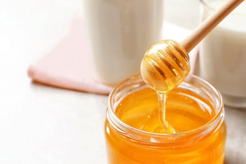 倾吐从浸染工的蜂蜜入瓶子 免版税库存照片