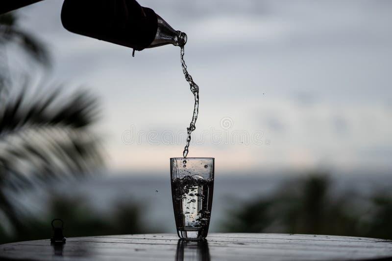 倾吐从瓶的水在自然背景的玻璃 图库摄影