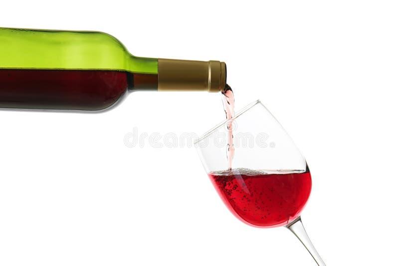 倾吐从瓶的红酒到在白色背景的玻璃里 免版税库存图片