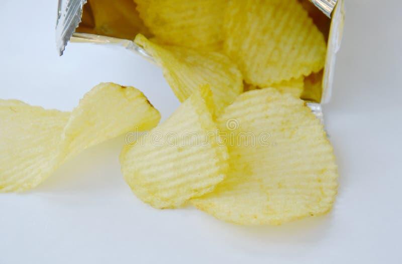 倾吐从铝芯的土豆片包装在白色背景 库存照片