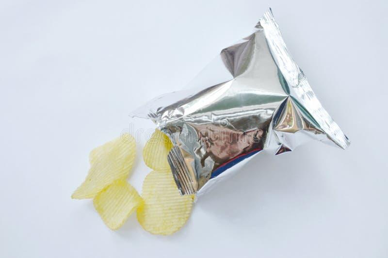 倾吐从铝芯的土豆片包装在白色背景 库存图片