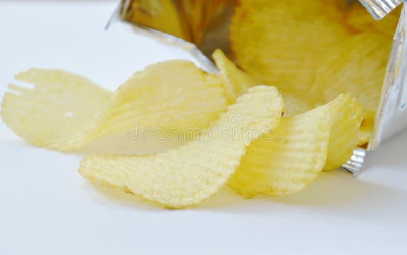 倾吐从铝芯的土豆片包装在白色背景 免版税库存照片