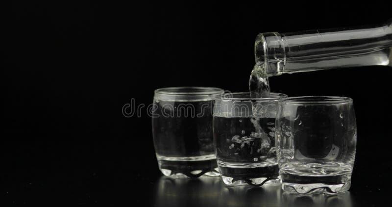 倾吐伏特加酒射击从一个瓶的到反对黑背景的玻璃里 免版税库存照片