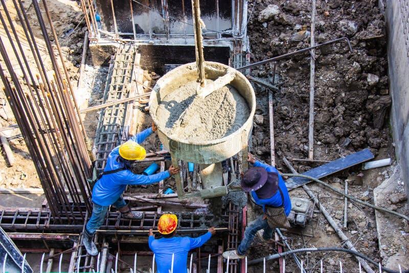 倾吐入基础模板的工作者倾吐的水泥在修造的区域在工地工作 免版税库存照片