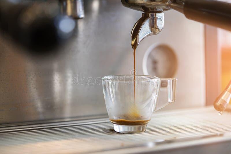 倾吐到从咖啡机器的杯子的浓咖啡特写镜头 小B 库存照片