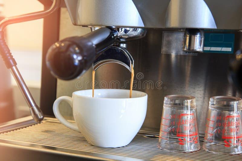 倾吐到从咖啡机器的杯子的浓咖啡特写镜头 小B 库存图片