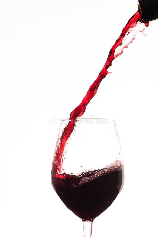 倾吐在一个酒杯的红葡萄酒,在白色背景 免版税库存照片