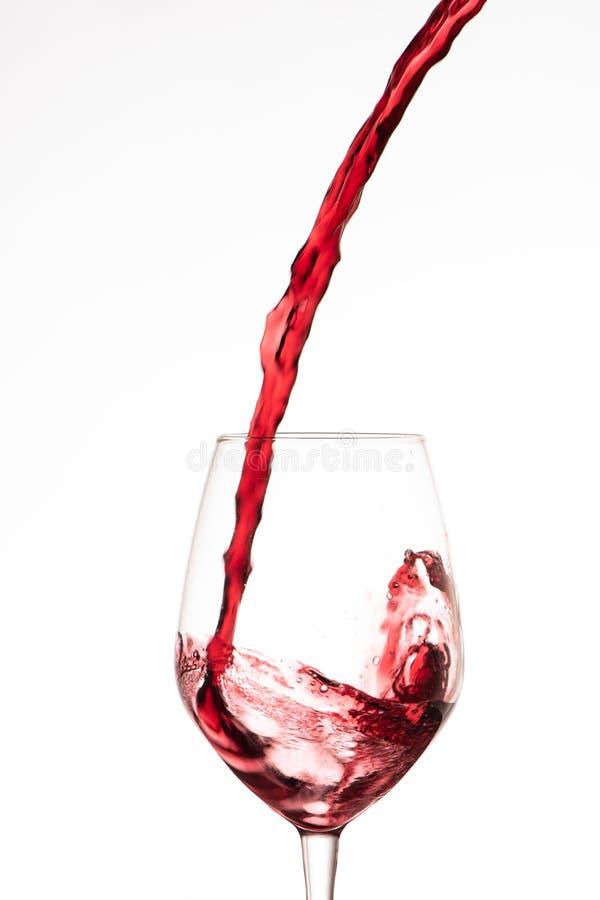 倾吐在一个酒杯的红葡萄酒,在白色背景 库存照片