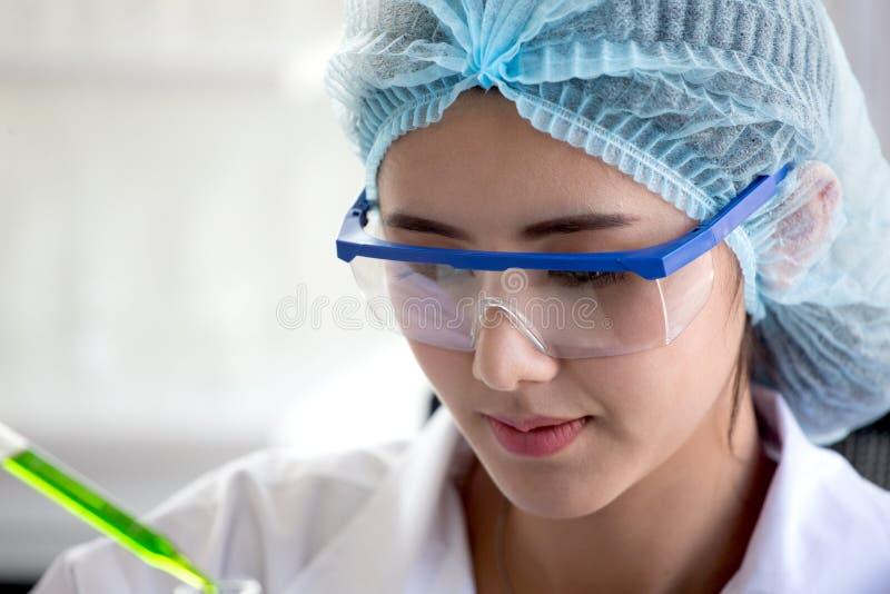 倾吐在一支管的亚裔妇女科学家研究和反应妇女液体在实验室,科学生物医学化学 免版税图库摄影