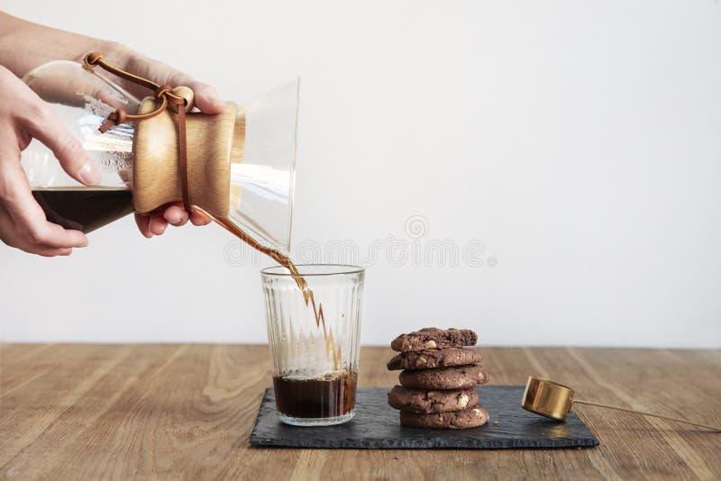 倾吐在咖啡酿造方法Chemex,妇女手举行一个玻璃碗,静物画用在木桌上的果仁巧克力曲奇饼 免版税库存照片
