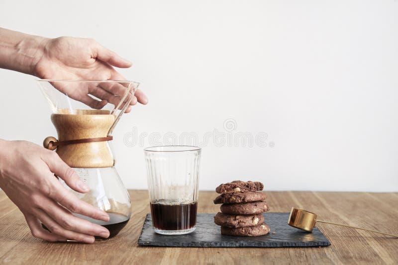 倾吐在咖啡酿造方法Chemex,妇女手举行一个玻璃碗,静物画用在木桌上的果仁巧克力曲奇饼 免版税图库摄影