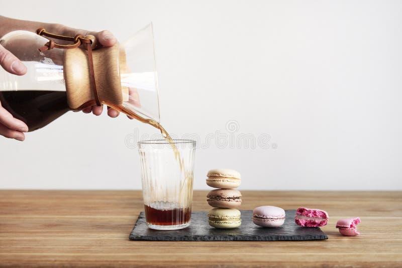 倾吐在咖啡酿造方法Chemex,妇女手举行一个玻璃碗,静物画用在木桌上的果仁巧克力曲奇饼 图库摄影