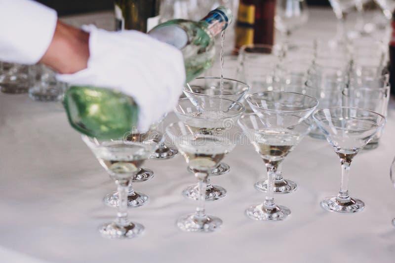 倾吐在水晶玻璃的侍者马蒂尼鸡尾酒在桌党在结婚宴会 马蒂尼鸡尾酒在酒精酒吧的行饮料 圣诞节和 免版税库存照片