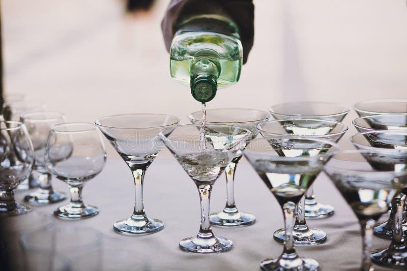 倾吐在水晶玻璃的侍者马蒂尼鸡尾酒在桌党在结婚宴会 马蒂尼鸡尾酒在酒精酒吧的行饮料 圣诞节和 免版税库存图片