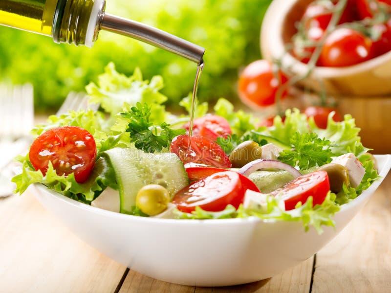倾吐在沙拉的橄榄油 免版税库存图片