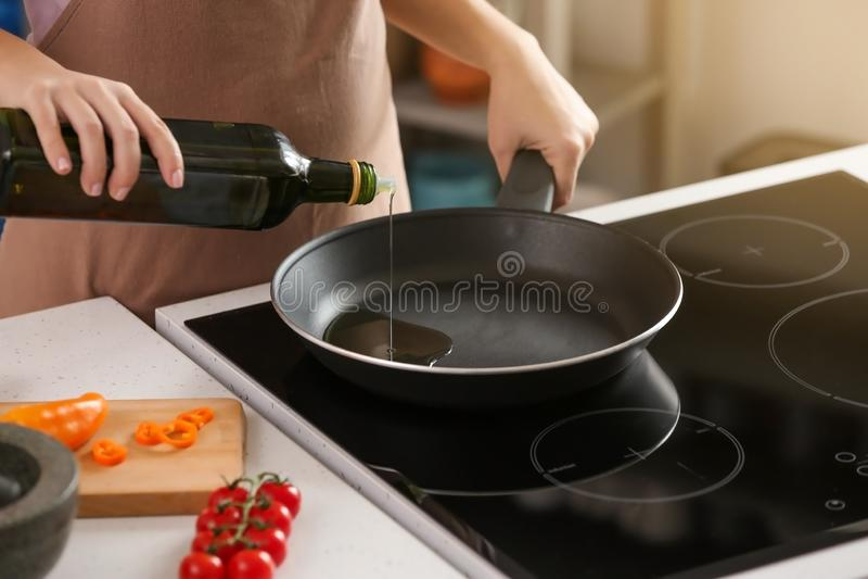 倾吐在煎锅上的妇女橄榄油在火炉 图库摄影