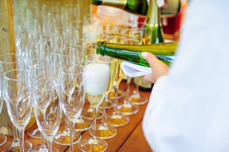 倾吐在玻璃的侍者个人服务的香宾 在事件的承办酒席服务,合作会议,党,婚礼 有选择性的fo 免版税库存照片