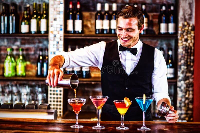 倾吐在玻璃的侍酒者橙色马蒂尼鸡尾酒饮料 库存照片