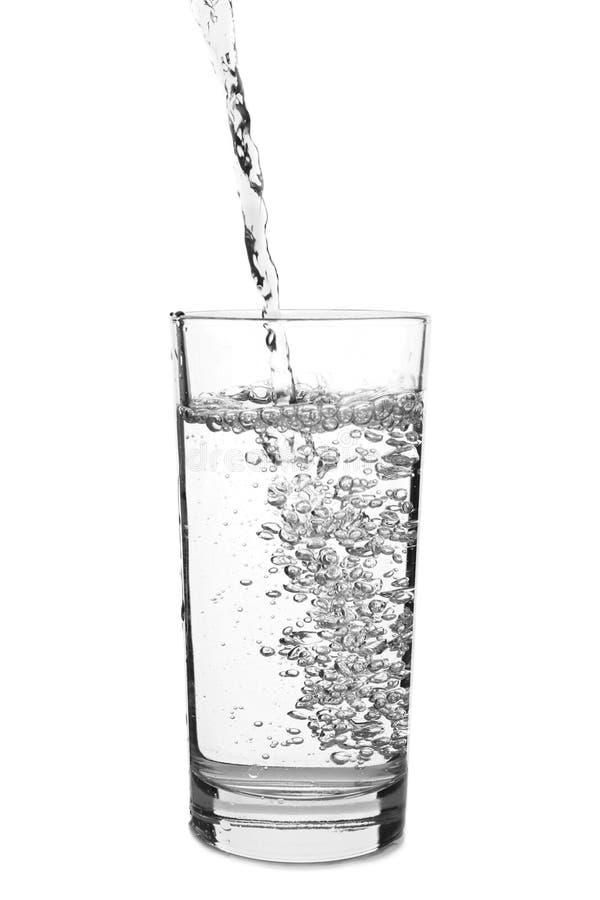 倾吐在玻璃的水在白色背景 库存图片