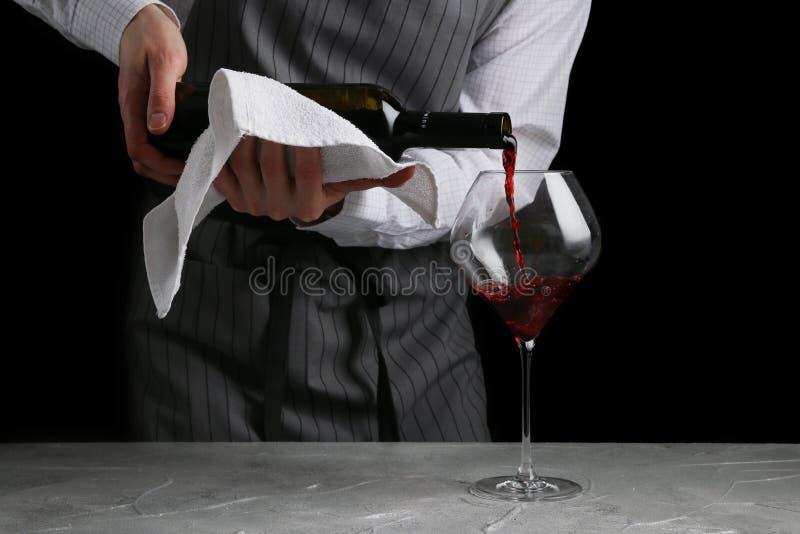 倾吐在玻璃的红酒 侍者概念的侍酒者在黑背景 免版税库存图片