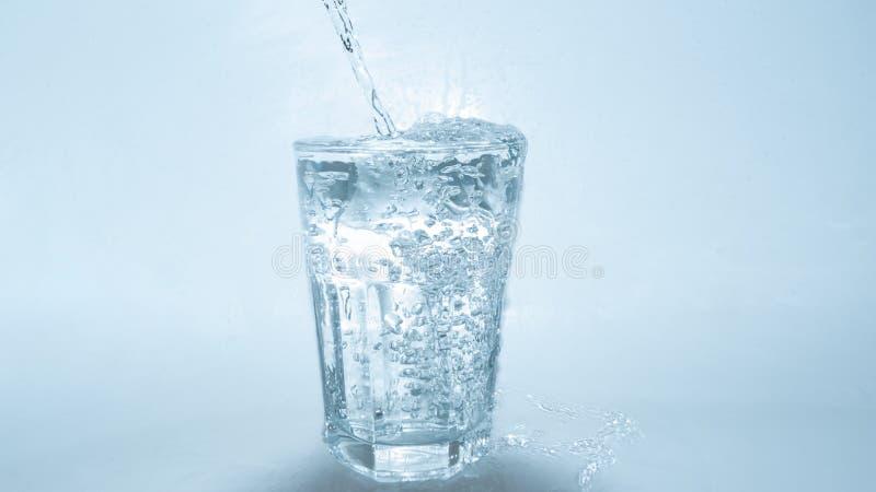 倾吐在白色背景的玻璃的水 免版税图库摄影