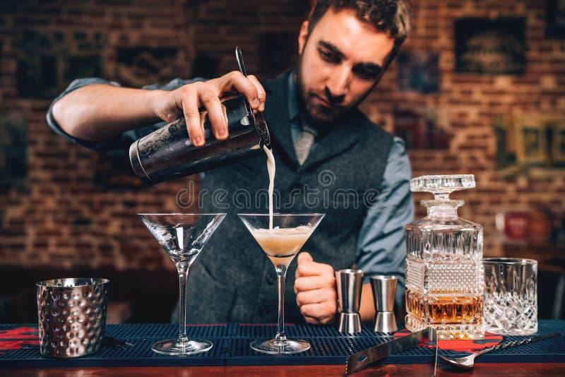 倾吐在酒吧的男服务员画象花梢鸡尾酒在党 曼哈顿鸡尾酒饮料在夜总会 库存图片