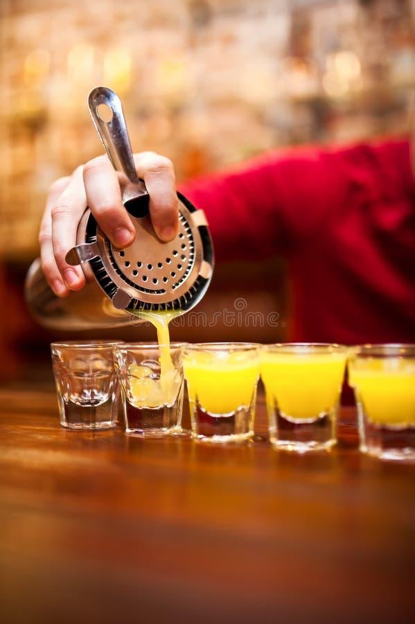 倾吐强的酒精饮料的侍酒者入在b的小玻璃 免版税库存照片