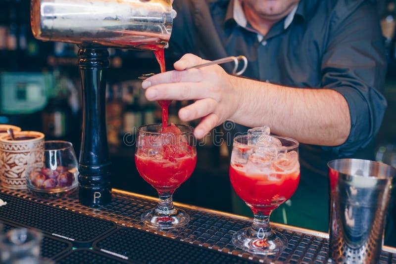倾吐桃红色的鸡尾酒的侍酒者使用在酒吧柜台的过滤器甜精神水多的饮料 男服务员背景视图 复制得过去 免版税库存照片