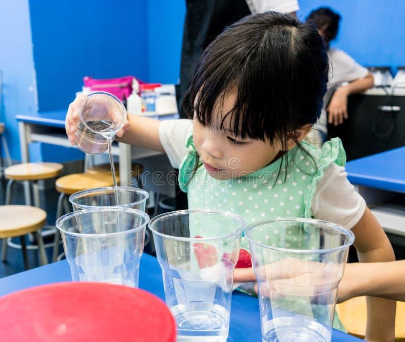 倾吐清楚的解答的幼儿园女孩入在蓝色tabl的一个杯子 免版税库存照片