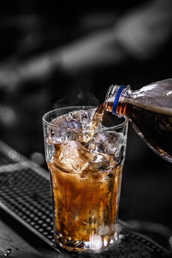 倾吐的可乐到玻璃里 免版税图库摄影