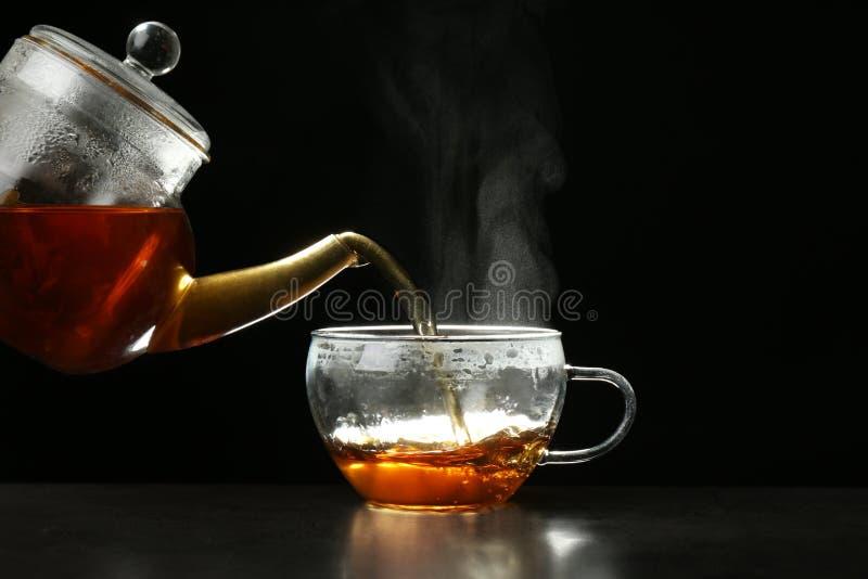 倾吐的可口热的茶到在桌上的玻璃杯子里反对黑暗 库存图片