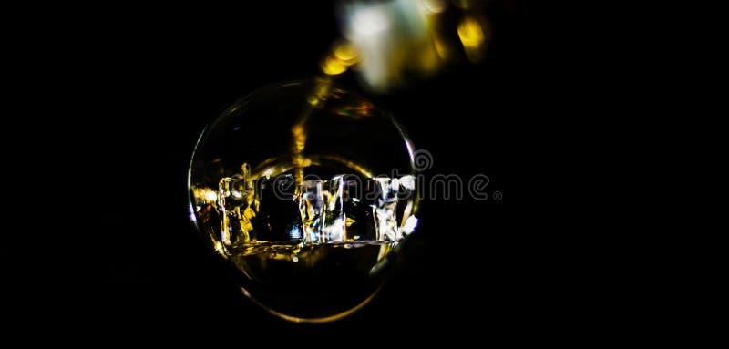 倾吐的唯一麦芽威士忌到玻璃里,金黄颜色威士忌酒 免版税图库摄影