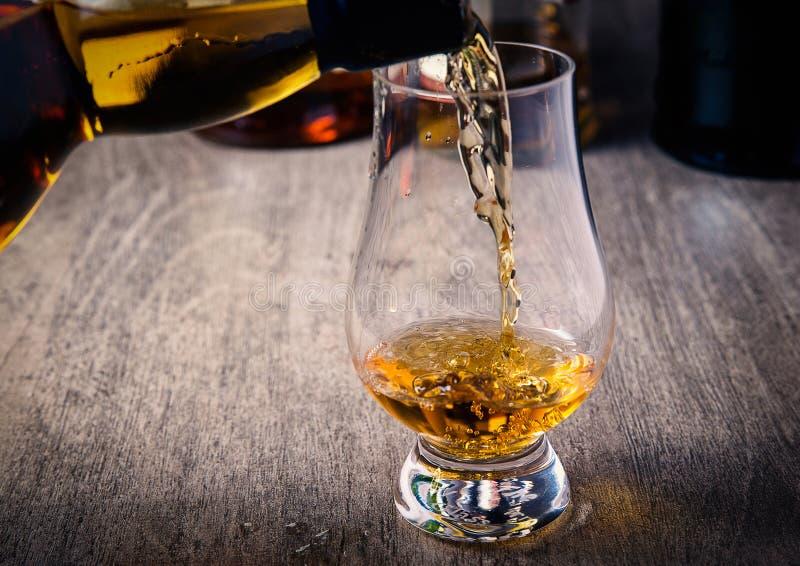 倾吐的唯一麦芽苏格兰威士忌酒到威士忌酒玻璃里 库存图片