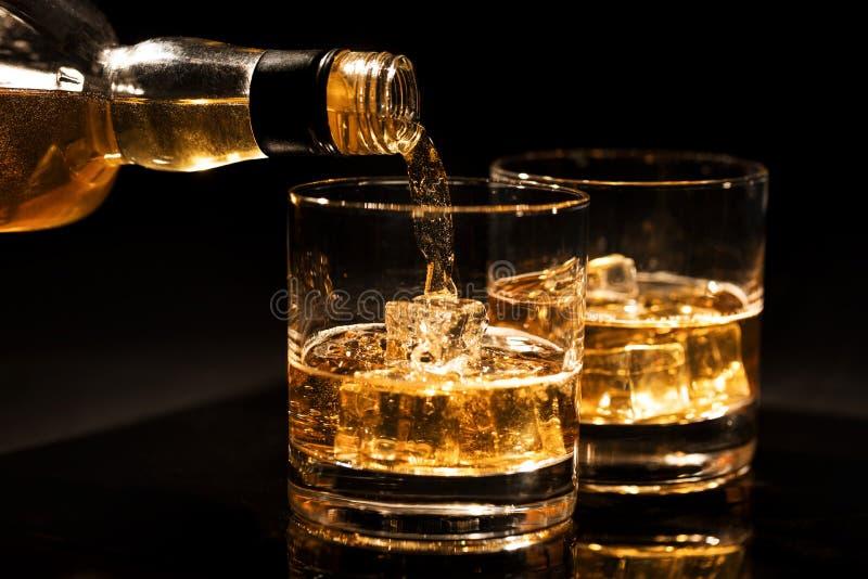 倾吐的威士忌酒到从瓶的一块玻璃里有在黑色的冰块的 库存图片