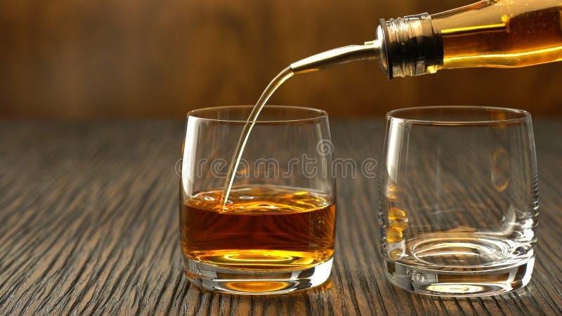 倾吐的威士忌酒到在一张木桌上的玻璃里 库存图片