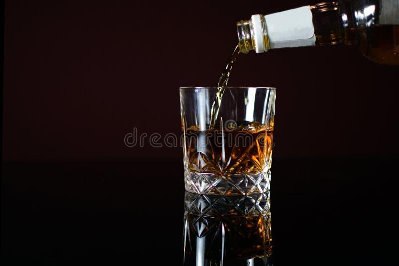 倾吐的威士忌酒到玻璃里 库存照片