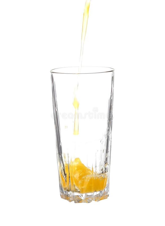 倾吐的橙汁到在白色隔绝的玻璃里 免版税图库摄影