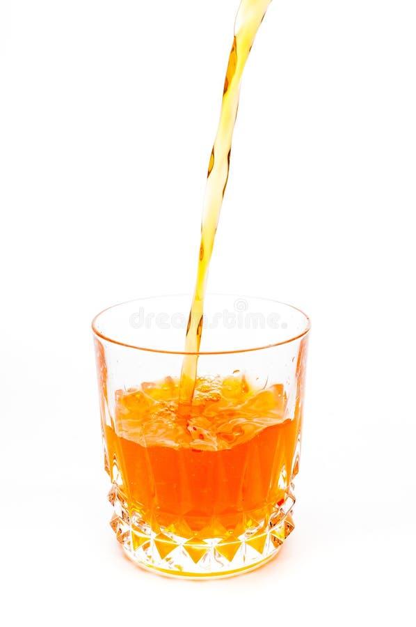 倾吐的橙汁到被隔绝的玻璃里 免版税图库摄影