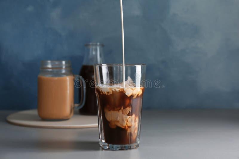 倾吐的牛奶到玻璃里用冷的酿造咖啡 免版税库存照片
