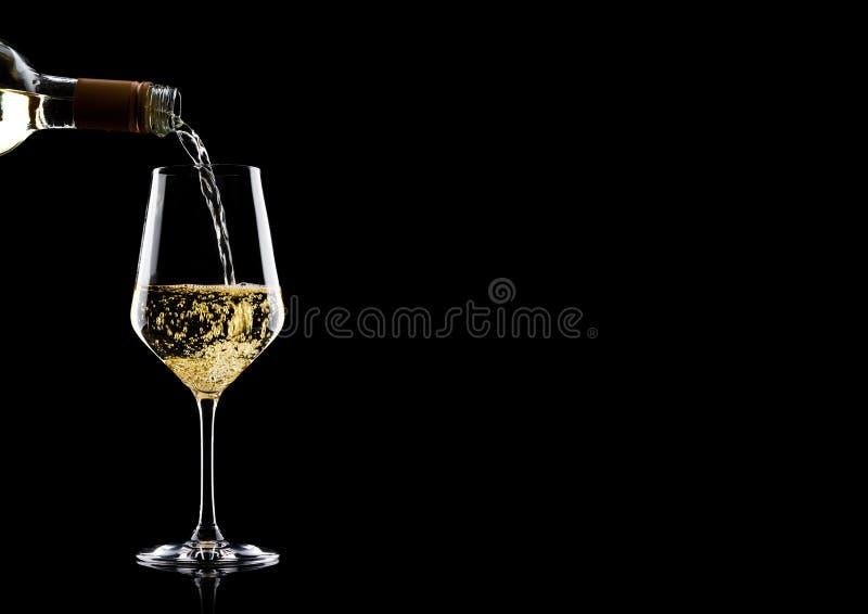 倾吐的白葡萄酒从瓶到在黑色的玻璃与您的文本的空间 免版税库存照片