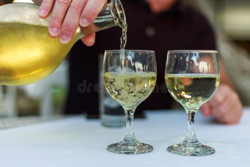 倾吐的白葡萄酒到反对木桌的玻璃里 免版税库存照片