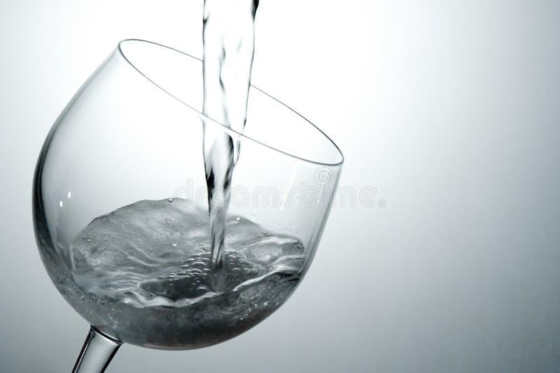 倾吐的白葡萄酒到玻璃里 图库摄影