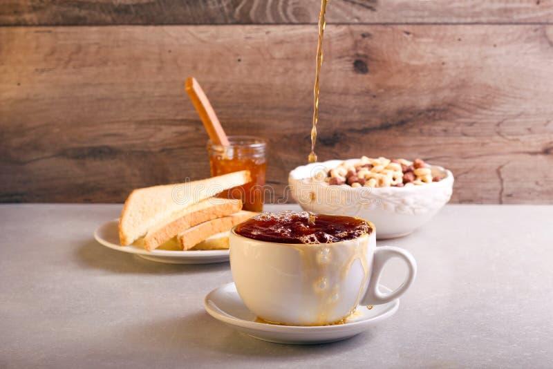倾吐的红茶到杯子里 免版税库存照片