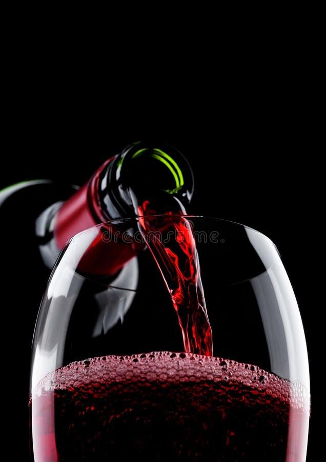 倾吐的红葡萄酒从瓶到在黑色的玻璃 库存图片