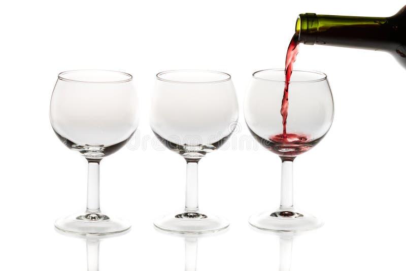 倾吐的红葡萄酒到从瓶的玻璃里 图库摄影