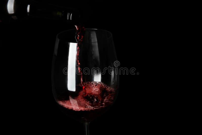 倾吐的红葡萄酒到在黑背景的玻璃里, 库存图片