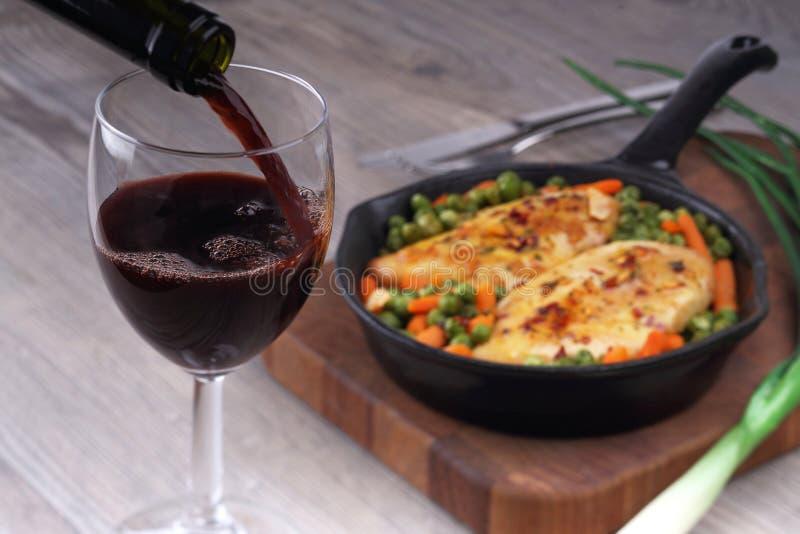 倾吐的红葡萄酒和食物 免版税库存照片